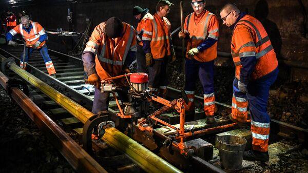 Рабочие во время замены шпал в тоннеле на станции Красносельская