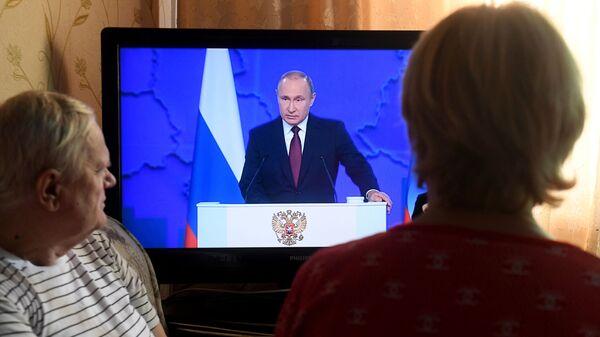 Жители Казани смотрят телевизионную трансляцию ежегодного послания президента РФ Владимира Путина к Федеральному собранию