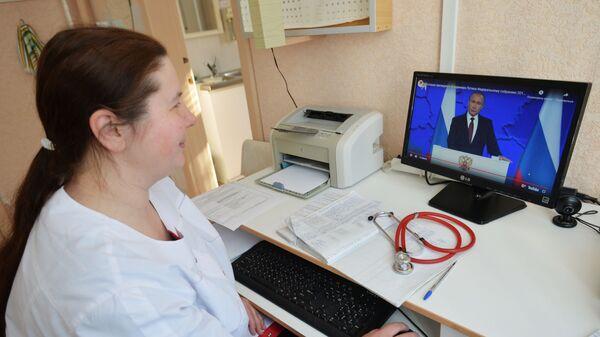 Врач смотрит трансляцию ежегодного послания президента РФ Владимира Путина к Федеральному собранию
