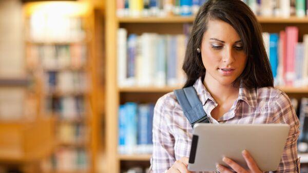 Девушка с планшетом в библиотеке
