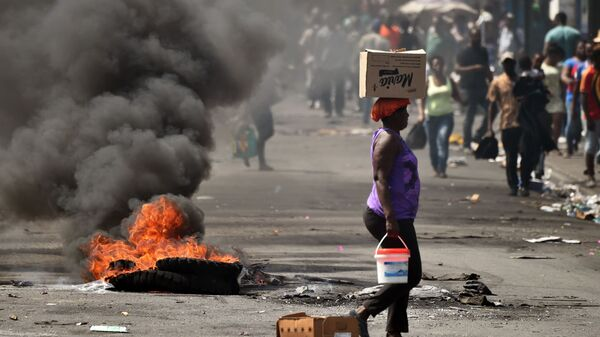 Женщина идет по улице во время беспорядков в столице Гаити Порт-о-Пренсе