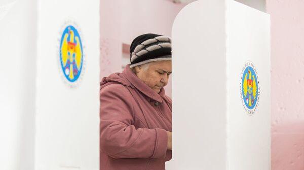 Женщина голосует на парламентских выборах на избирательном участке в Кишиневе
