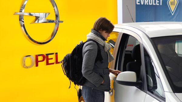 Посетительница осматривает автомобиль в автосалоне