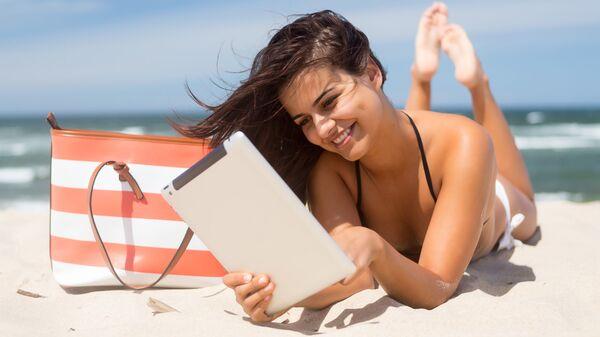 Девушка с планшетом на пляже