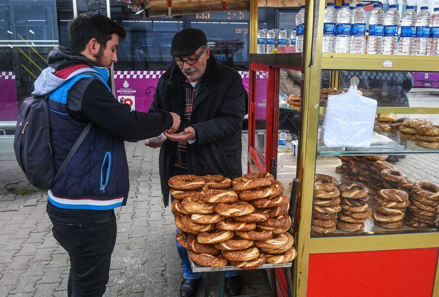 Мужчина покупает хлебобулочные изделия на одной из улиц в районе Кадыкей города Стамбул