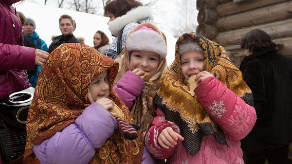 Дети едят блины во время праздничных гуляний на Масленицу