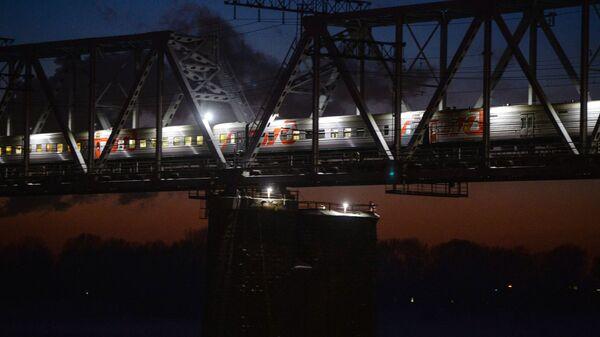 Пассажирский поезд дальнего следования на железнодорожном мосту через реку Обь