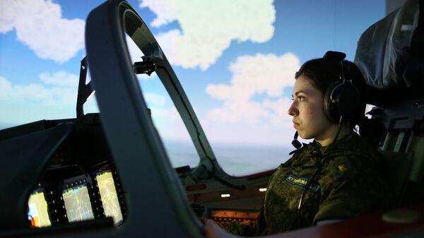 Девушка-курсант во время занятий на летном тренажерном комплексе в высшем военном авиационном училище летчиков