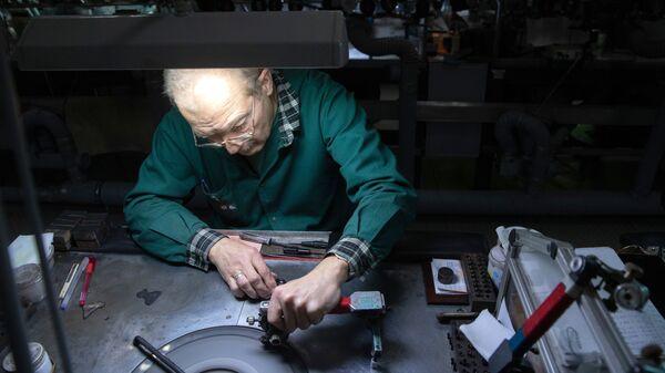 Сотрудник шлифует бриллиант в цехе огранки ООО Бриллианты Алроса в Москве