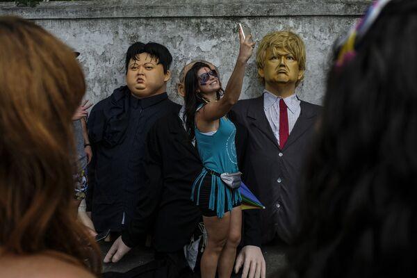 Девушка делает селфи с куклами, изображающими Ким Чен Ына и Дональда Трампа, во время карнавала в Бразилии