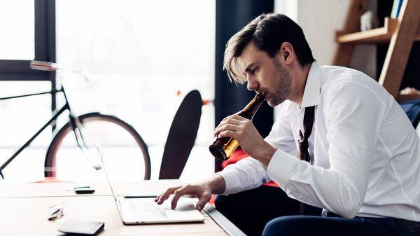 Человек с бутылкой пива за ноутбуком