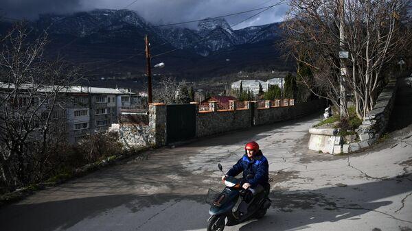 Мужчина едет на мопеде в Гурзуфе в Крыму