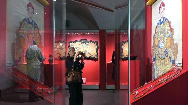 Посетительница у Портрета императора Цзяцина в парадном одеянии (эпоха Цин, правление Цзяцин, 1796-1821 гг.) на выставке Сокровища императорского дворца Гугун