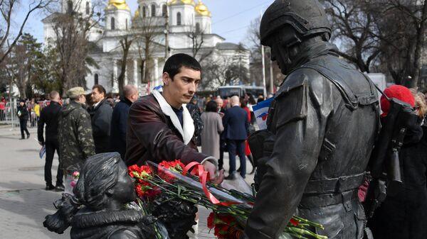 Мужчина оставляет цветы у памятника Вежливым людям во время мероприятий, посвященных 5-й годовщине Общекрымского референдума 2014 года и воссоединения Крыма с Россией, в сквере Республики в Симферополе