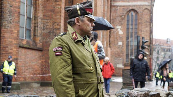 Участник перед началом марша легионеров Waffen SS у церкви Святого Петра в Риге. 16 марта 2019