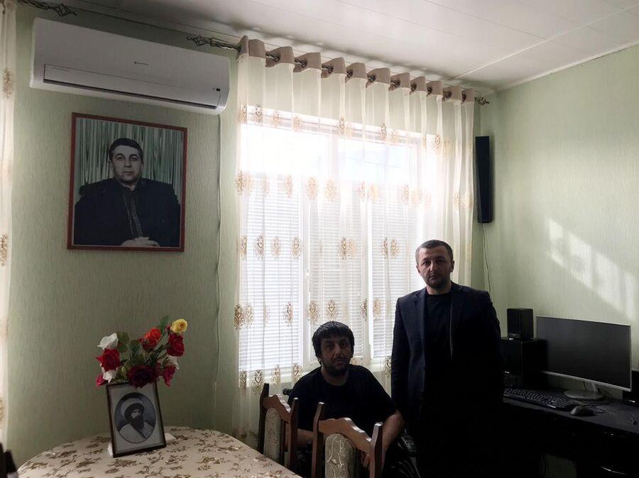 Магомед Гамзатов вместе со старшим братом на фоне портрета отца, убитого боевиками