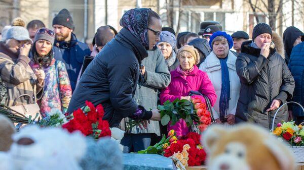 Девушка возлагает цветы к мемориалу в память о жертвах пожара в торгово-развлекательном центре Зимняя вишня в Кемерово