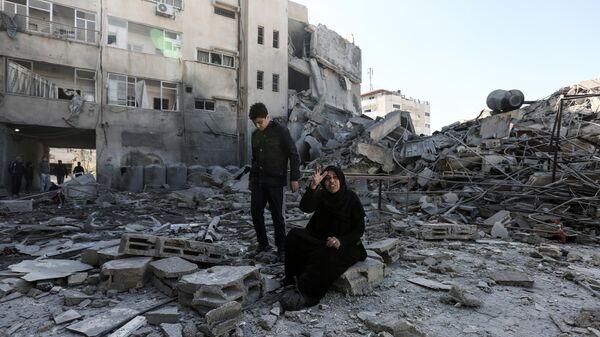 Палестинцы возле здания, разрушенного в результате ударов Израиля