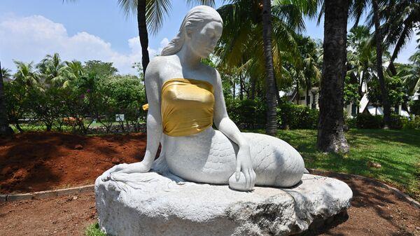 В парке Ancol Dreamland грудь статуи русалки прикрыли золотой тканью. Джакарта, Индонезия