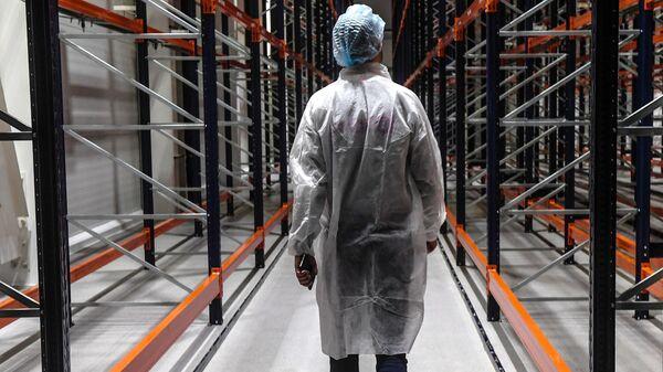 Сотрудник идет по складу готовой продукции на фармацевтическом предприятии