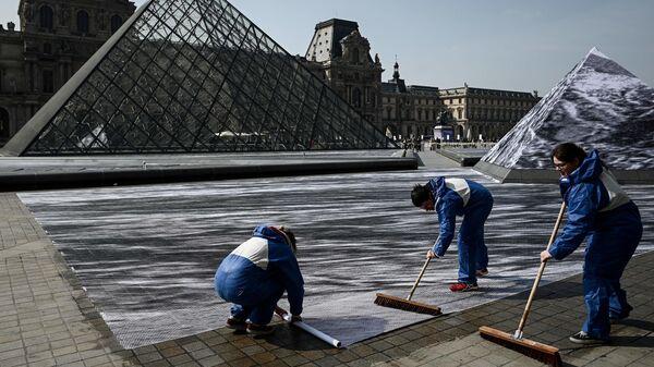 Волонтеры во время подготовки инсталляции французского современного художника и фотографа Жана Рене в главном дворе Лувра в Париже. 28 марта 2019
