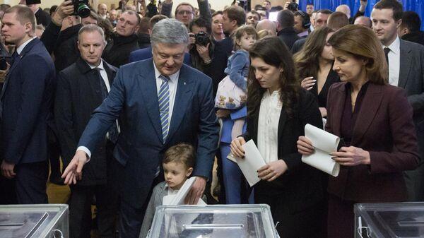 Действующий президент Украины Петр Порошенко с супругой и детьми на избирательном участке в Киеве во время голосования на президентских выборах