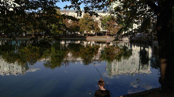 Девушка сидит на берегу пруда на Чистопрудном бульваре в Москве