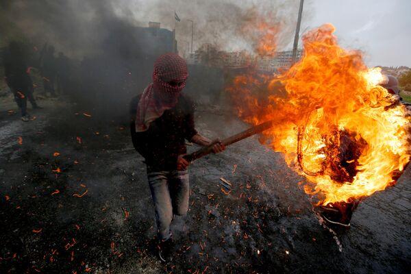 Палестинец во время столкновений с израильскими войсками после демонстрации, посвященной Дню земли