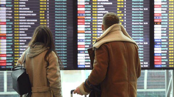 Пассажиры смотрят информационное табло в аэропорту Домодедово