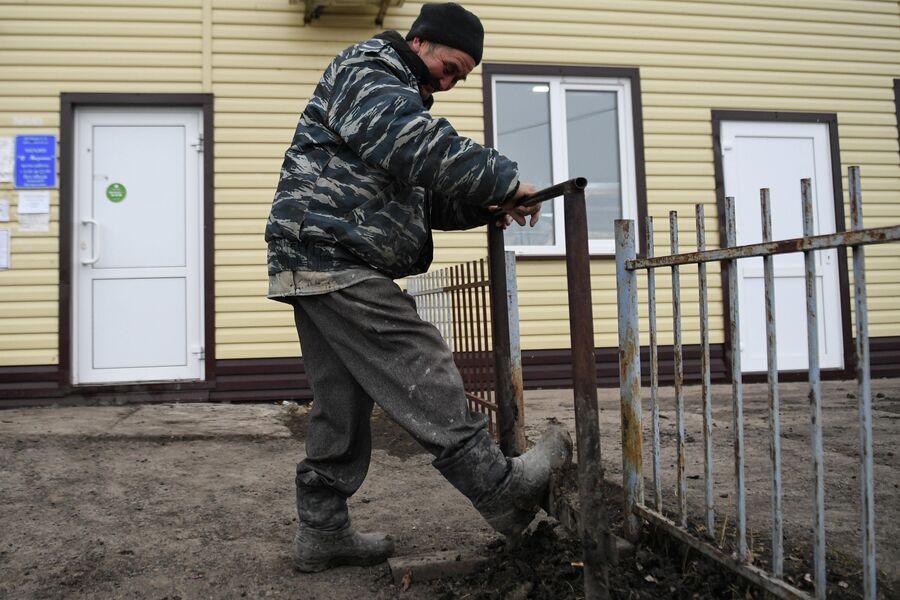 Мужчина очищает обувь от грязи в деревне Аполлоновка