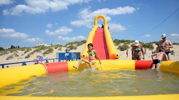Дети на водной горке на пляже в Анапе