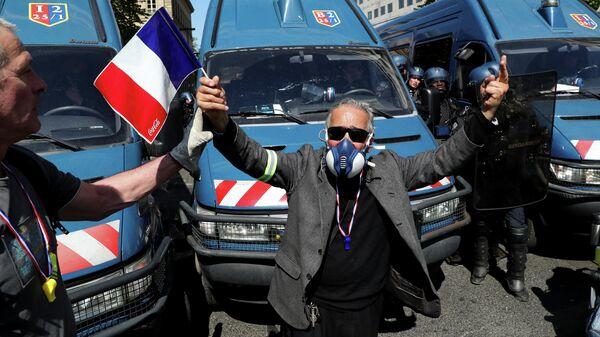 Мужчина с французским флагом во время 23-го общенационального протеста по субботам движения желтых жилетов в Париже, Франция. 20 апреля 2019
