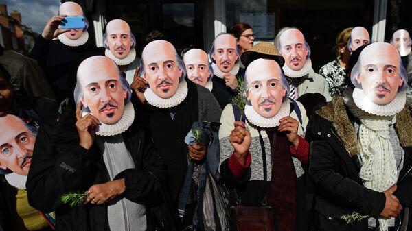Участники торжественных мероприятий в масках с изображением Уильяма Шекспира, посвященных 400-летию его смерти, в городе Стратфорд-на-Эйвоне, Великобритания