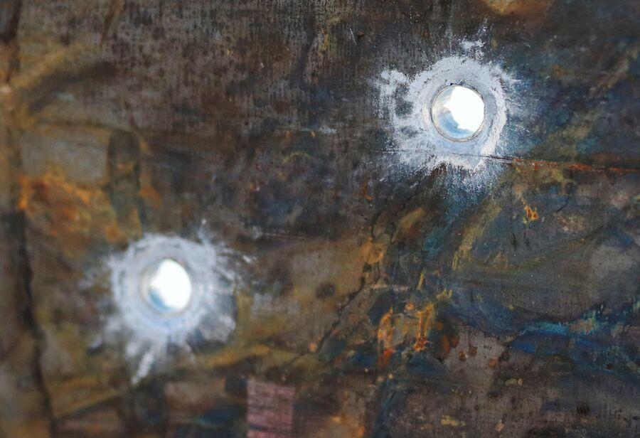 Металлический лист толщиной 4 мм, пробитый с расстояния 25 метров из самозарядного пистолета Удав