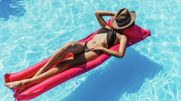 Девушка отдыхает в бассейне. Архивное фото