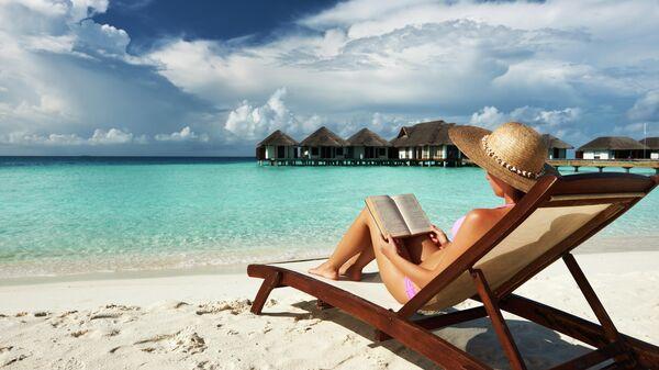 Женщина читает книгу на берегу