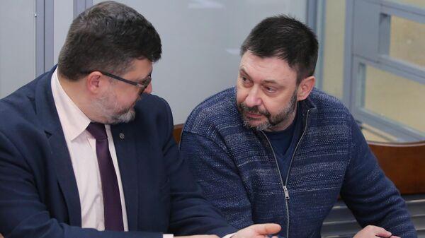 Руководитель портала РИА Новости Украина Кирилл Вышинский (справа) и адвокат Андрей Доманский