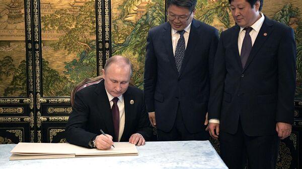 Президент РФ Владимир Путин оставляет запись в книге почетных гостей во время рабочего завтрака с председателем Китайской народной республики (КНР) Си Цзиньпином в Пекине