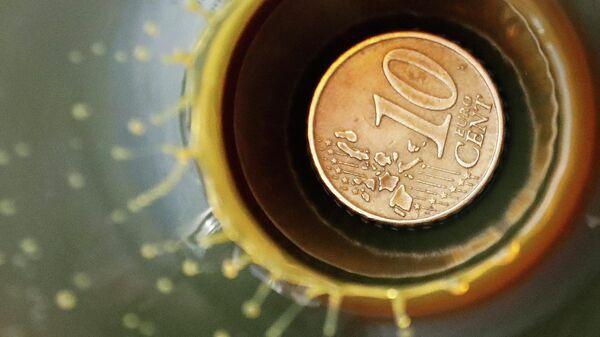 Монета 10 центов внутри колбы с нефтью