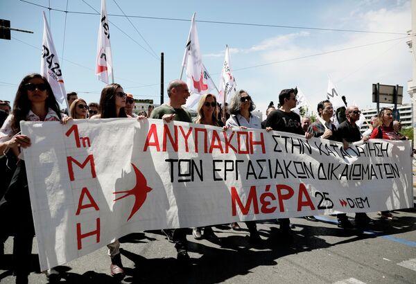 Участники первомайской демонстрации в Афинах, протестующие против экономической политики правительства и выступающие за реализацию прав трудящихся на достойную зарплату и социальную защиту