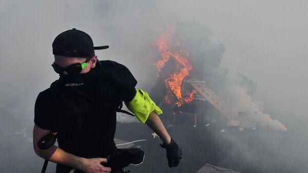 Участник уличных беспорядков у горящей баррикады на улице Парижа