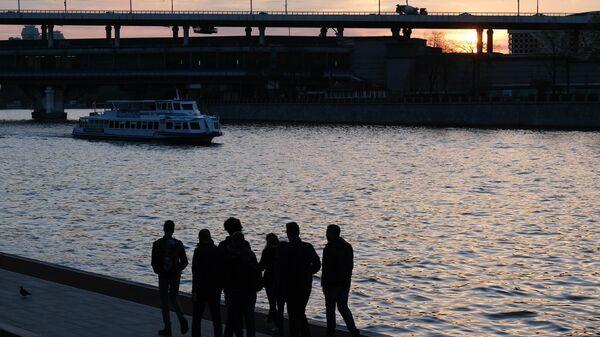Люди гуляют по набережной Москвы-реки. На втором плане: Лужнецкая эстакада.