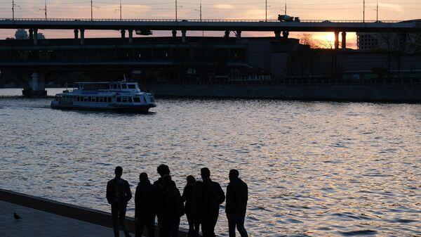 Люди гуляют по набережной Москвы-реки