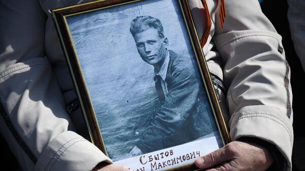Портрет ветерана войны в руках участника акции Бессмертный полк в Чите