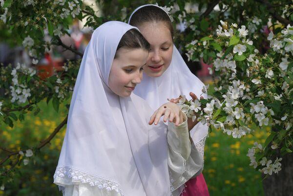 Девочки в платках возле цветущего дерева в день праздника Святых Жён-Мироносиц в духовном центре старообрядчества Рогожская слобода в Москве