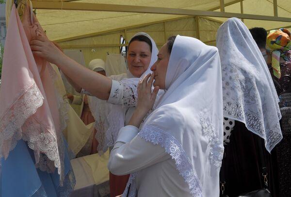 Женщина выбирает платок в день праздника Святых Жён-Мироносиц в духовном центре старообрядчества Рогожская слобода в Москве