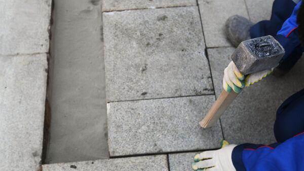 Рабочий укладывает тротуарную плитку на Никитском бульваре в Москве