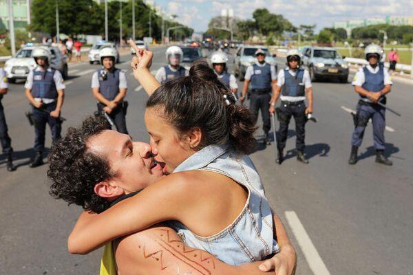 Пара целуется во время акции протеста студентов и преподавателей в Бразилии