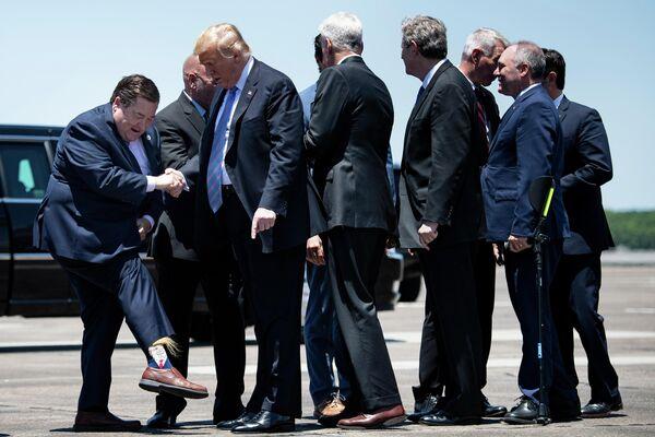 Вице-губернатор американского штата Луизиана Билли Нангессер показывает носки во время встречи с президентом США Дональдом Трампом в аэропорту Лейк-Чарлз