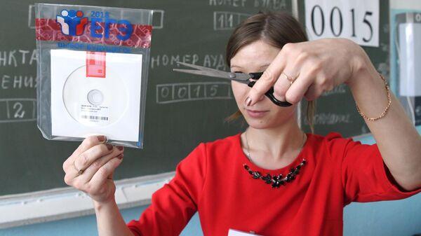 Учитель вскрывает пакет с диском, на котором содержатся задания для ЕГЭ
